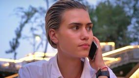 De moderne vrouw zit op ladder, die op telefoon in avond spreken, vertroebelde lichten op achtergrond stock video