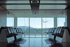 De moderne zitkamer van het luchthavenvertrek met vliegtuig het opstijgen Stock Afbeelding