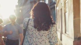 De modieuze aantrekkelijke donkerbruine bedrijfsdame, met schitterend kapsel en luxueus kijkt De schitterende jonge vrouw loopt n stock video