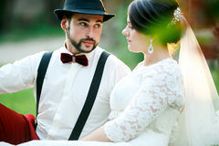 De modieuze bruid en de bruidegom zitten op gras in stralen van het plaatsen van zonlicht De jonggehuwden koppelen Stock Foto's