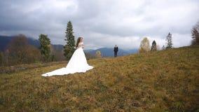 De modieuze bruidegom komt aan zijn mooie aantrekkelijke bruid in modieuze lange kleding die zich op de bovenkant van de herfst b stock video
