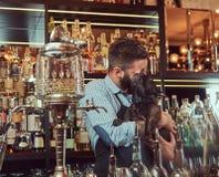 De modieuze brutale barman in een overhemd en een schort houdt volbloed- zwarte pug bij bar tegenachtergrond royalty-vrije stock afbeeldingen