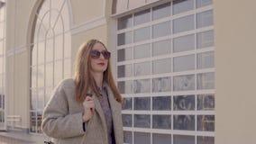 De modieuze dame wandelt alleen in openlucht in stad, die in laag verpakken stock footage