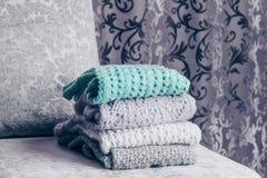 De modieuze gebreide pastelkleur kleurde sweaters die in stapel op fluweelachtige stoffenbank worden gevouwen met een uitstekende stock fotografie
