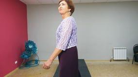 De modieuze hogere vrouw stelt en vervuilt op podium bij modeshow Bejaarde mannequin die nieuwe kleding op loopbrug tonen stock videobeelden