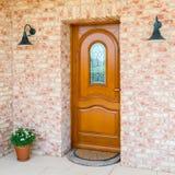 De modieuze houten voorzijde - ingangsdeur in een losgemaakt huis - bedt in stock afbeeldingen