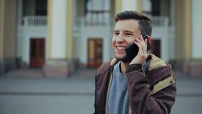 De modieuze jonge aantrekkelijke mens spreekt op de telefoon stock video