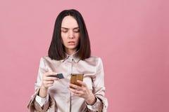 De modieuze jonge donkerbruine vrouw met een ernstige geconcentreerde uitdrukking gebruikt kaart om voor aankopen in Internet te  royalty-vrije stock fotografie