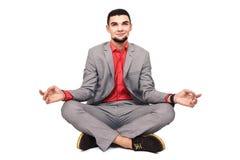 De modieuze jonge gebaarde kerel in een grijs kostuum mediteert zitting in de lotusbloempositie royalty-vrije stock foto