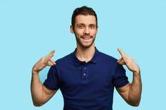 De modieuze jonge knappe mens glimlacht en richt op zijn blauwe t-shirt stock foto's