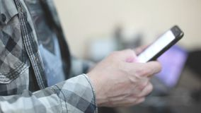 De modieuze jonge mens in een plaidoverhemd gebruikt een smartphone stock videobeelden