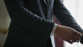 De modieuze jonge mens met gouden horloge op linkerhand maakt jasje en kokers van wit overhemd recht stock footage