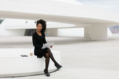De modieuze jonge professionele vrouw die van het afrohaar tablet gebruiken royalty-vrije stock foto