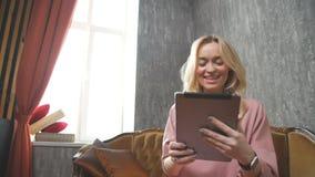De modieuze jonge vrouw in een hoed geniet van mededeling in een tablet stock videobeelden