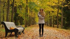 De modieuze jonge vrouw voelt koud en vraag door mobiele dichtbijgelegen een bank in de herfstpark stock footage