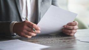 De modieuze jonge zakenman in grijs kostuum ondertekent contract stock footage