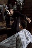 De modieuze kapper gekleed in zwarte kleren droogt man haar in een herenkapper royalty-vrije stock afbeelding