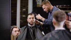 De modieuze kapper scheert tempels met hairclipper van een gebaarde mensenzitting op leunstoel in de herenkapper en bekijkt bij stock video