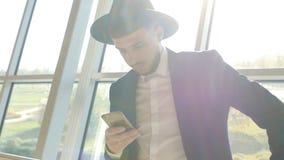 De modieuze Kaukasische mens in zwarte kostuum en hoed houdt telefoon in zijn hand en gelezen informatie terwijl het zijn bij de  stock videobeelden