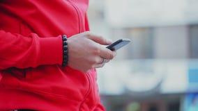 De modieuze kerel gebruikt de telefoon, leest het nieuws, bekijkt de foto stock videobeelden