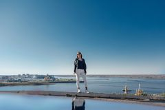 De modieuze meisje status op een berg, blauwe hemel dacht in het water na stock foto