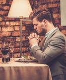 De modieuze mens bidt vóór maaltijd bij restaurant Stock Fotografie