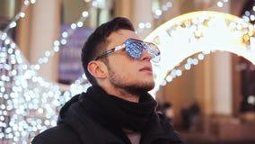 De modieuze mens bij viert het nieuwe die jaar, de stadskerstboom, slingers en de lichten in de weerspiegelde zonnebril wordt de  stock videobeelden