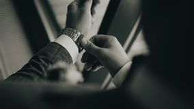 De modieuze mens zet een mechanisch horloge op zijn hand Hij bevindt zich voor een helder venster Close-up van de schouder Het sc stock footage