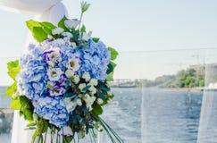 De modieuze, modieuze die ceremonie van de huwelijksboog met blauw wordt verfraaid en verschillende het wit bloeien Bloemen ontwe Royalty-vrije Stock Foto's
