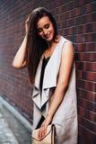 De modieuze modieuze jonge donkerbruine vrouw in een beige cardigan bevindt zich dichtbij een bakstenen muur met een koppeling of Stock Afbeeldingen
