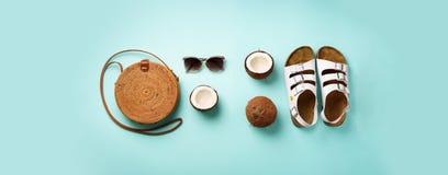 De modieuze rotanzak, kokosnoot, birkenstocks, palm vertakt zich, zonnebril op blauwe achtergrond banner Hoogste mening met exemp royalty-vrije stock afbeeldingen