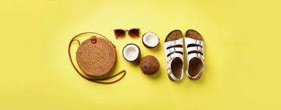 De modieuze rotanzak, kokosnoot, birkenstocks, palm vertakt zich, zonnebril op gele achtergrond banner Hoogste mening met exempla stock foto's