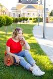 De modieuze tiener weared in jeans en rode T-shirtzitting op gras Stock Foto's