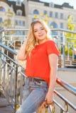 De modieuze tiener weared in jeans en rode T-shirtzitting op gras Royalty-vrije Stock Afbeeldingen