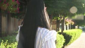 De modieuze vrouw in gestripte blouse loopt bij straat met kleine opslag in stad stock video