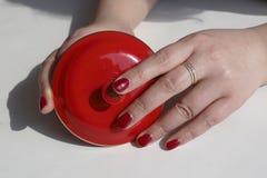 De modieuze vrouw schilderde rood nagellak, hand, twee handen die een rode dekking van de theekop houden Royalty-vrije Stock Foto's