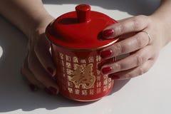 De modieuze vrouw schilderde rood nagellak, hand, twee handen die een rode theekoppen houden Royalty-vrije Stock Afbeelding