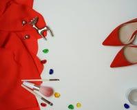 De modieuze vrouwelijke klerentoebehoren vormen uitrusting: de rode doek, schoenenmake-up borstelt de witte achtergrond van oorri royalty-vrije stock foto's