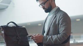 De modieuze zakenman in een kostuum gebruikt een gadget voor bedrijfskwesties stock video