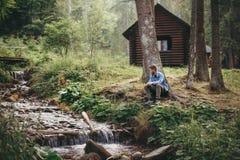 De modieuze zitting van de hipstermens en het ontspannen bij houten cabine in voorst gedeelte stock afbeelding