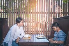 De moeder beschuldigt zeurt haar zoon omdat hij bij mobiele telefoon speelt stock foto