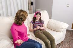 De moeder is boos met haar dochter Tienermeisje met roze headphon Stock Foto