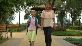 De moeder communiceert met zoon na school, aandacht aan kind, juiste opvoeding stock footage