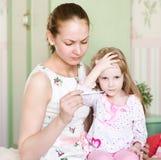 De moeder controleert temperatuur bij kind Stock Afbeelding