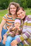 De moeder, de baby en de vader zitten op gras Royalty-vrije Stock Foto