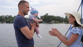 De moeder, de vader en weinig baby rusten op rivier, echtgenoot en vrouw met klein jong geitje op jacht, familiereis, mum, papa e stock footage