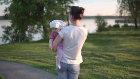 De moeder die haar baby in handen houden en daalt naar het meer, de zonsondergang en de lichten stock videobeelden
