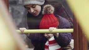 De moeder die haar glimlachende dochter, meisjesleeftijd die 3-4 helpen, warme kleren dragen beklimt op bars op de speelplaats Mo stock video