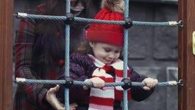 De moeder die haar glimlachende dochter, meisjesleeftijd die 3-4 helpen, warme kleren dragen beklimt op een netto kabel op de spe stock videobeelden