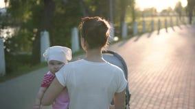De moeder die met baby in handen op de parkweg lopen, slowmotion schot, zon glanst stock footage